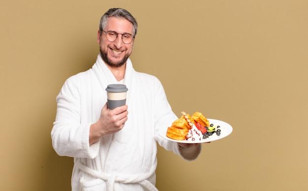 Homem de meia idade tomando waffles no café da manhã
