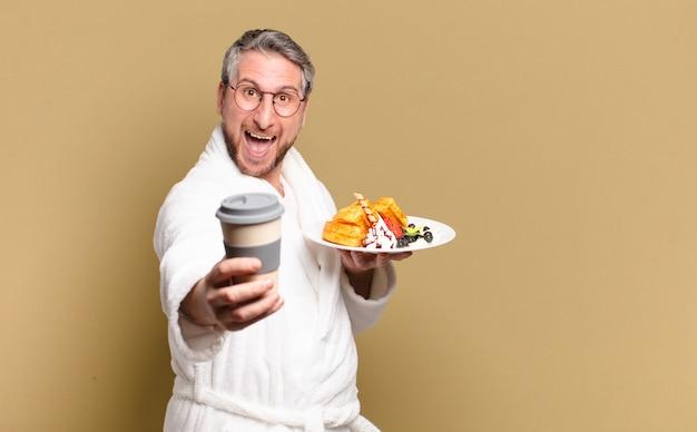 Homem de meia-idade tomando waffles no café da manhã