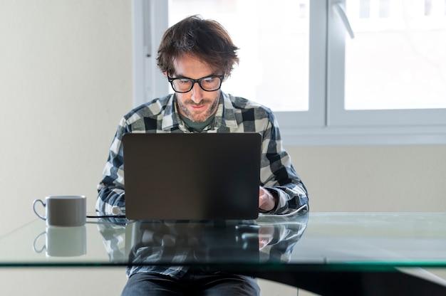 Homem de meia-idade trabalhando em casa no escritório do laptop. vista frontal