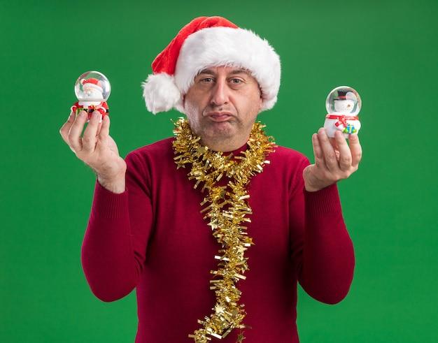 Homem de meia-idade usando chapéu de papai noel com enfeites de natal ao redor do pescoço e segurando globos de neve de natal com expressão cética