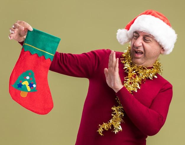 Homem de meia idade usando chapéu de papai noel com enfeites de natal ao redor do pescoço segurando uma meia de natal olhando para ele descontente e confuso fazendo gesto de defesa com a mão em pé sobre a parede verde
