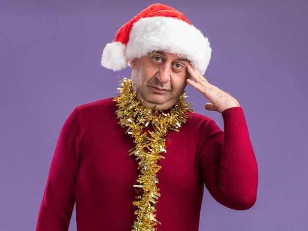 Homem de meia idade usando chapéu de papai noel de natal com enfeites em volta do pescoço e olhando para a câmera confuso com uma mão na cabeça em pé sobre um fundo roxo