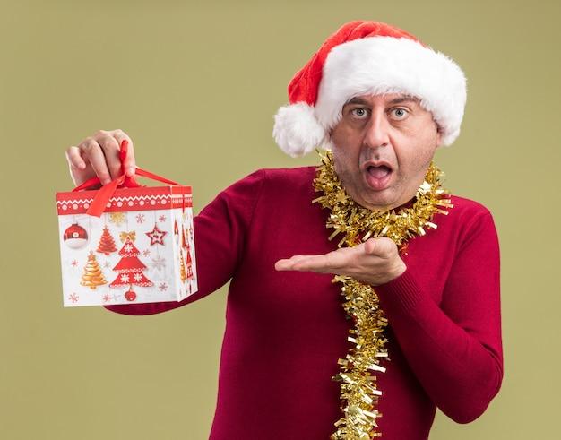 Homem de meia-idade usando chapéu de papai noel de natal com enfeites em volta do pescoço segurando um presente de natal e apresentando o braço da mão parecendo confuso em pé sobre um fundo verde