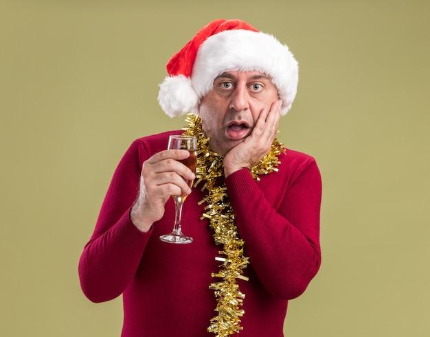 Homem de meia-idade usando chapéu de papai noel de natal com enfeites em volta do pescoço segurando uma taça de champanhe espantado e surpreso em pé sobre a parede verde
