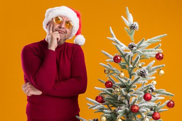 Homem de meia-idade usando chapéu de papai noel de natal com gola alta vermelha escura e óculos amarelos, olhando para cima com uma expressão pensativa com a mão no queixo ao lado de uma árvore de natal sobre fundo laranja
