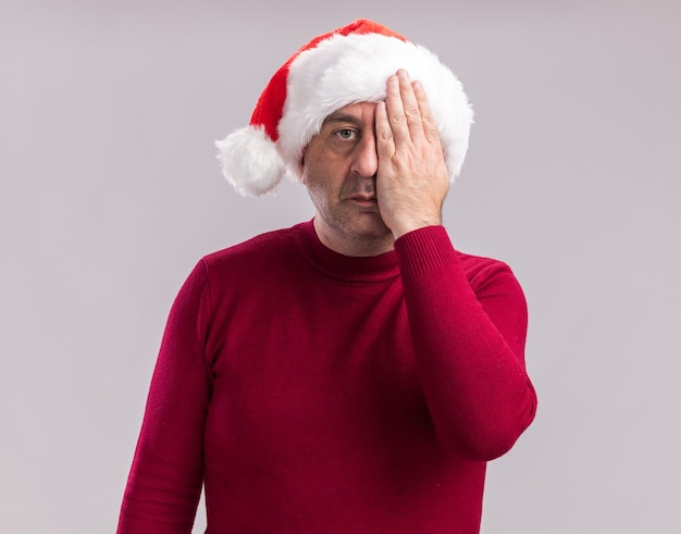 Homem de meia-idade usando chapéu de papai noel de natal com rosto sério cobrindo um ye com a mão em pé sobre uma parede branca