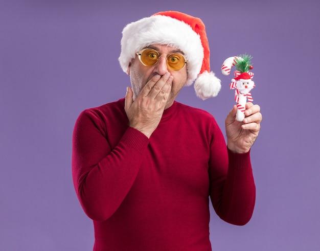 Homem de meia idade usando chapéu de papai noel de natal em óculos amarelos segurando uma bengala de doces de natal olhando para a câmera espantado, cobrindo a boca com a mão em pé sobre um fundo roxo