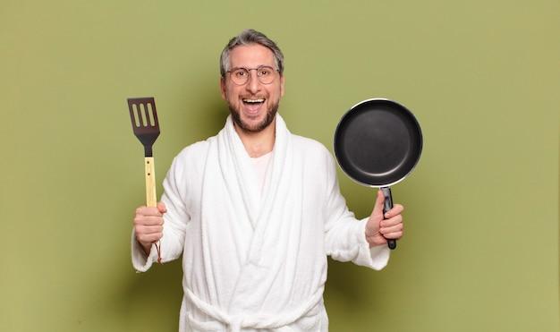 Homem de meia-idade usando roupão de banho e aprendendo a cozinhar com uma panela