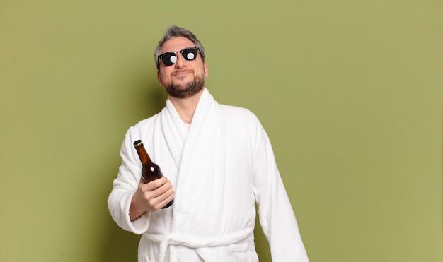 Homem de meia-idade usando roupão de banho e bebendo cerveja