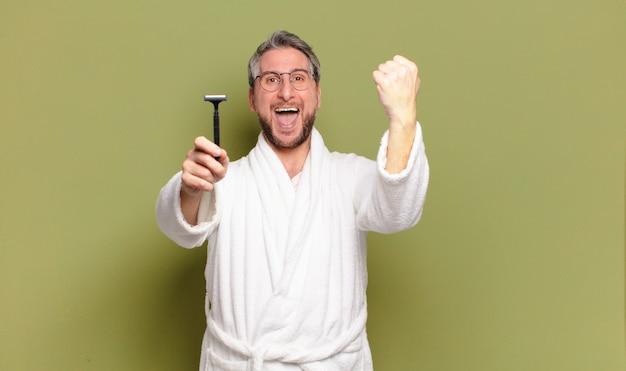 Homem de meia-idade usando roupão de banho e navalha