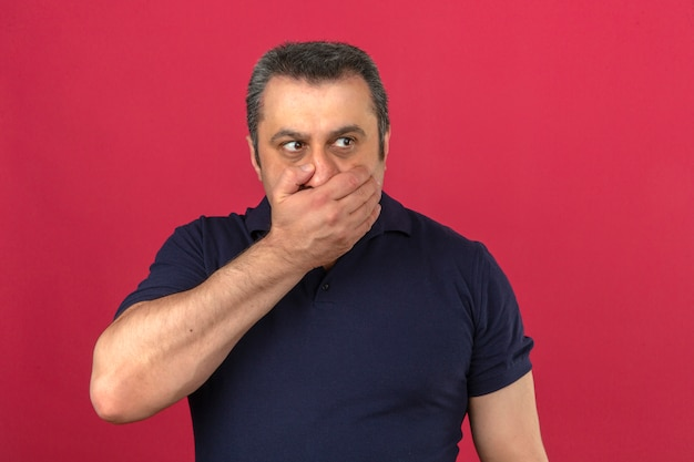 Homem de meia idade vestindo camisa polo cobrindo a boca com a mão com medo de manter informações secretas sobre parede rosa isolada