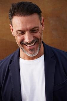 Homem de meia idade, vestindo uma jaqueta rindo feliz