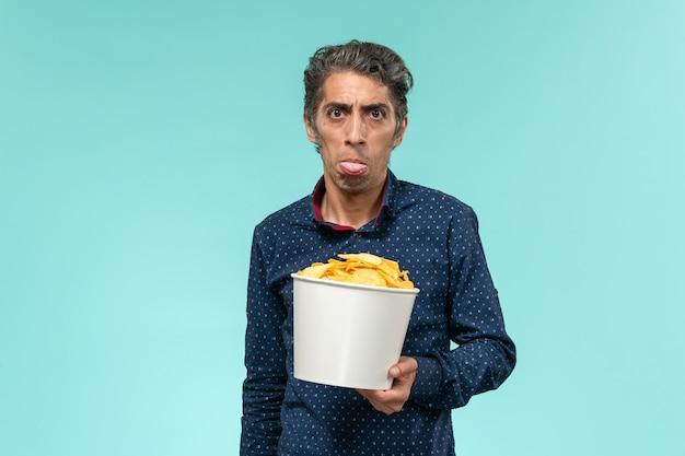 Homem de meia-idade, vista frontal, segurando cips e comendo na superfície azul