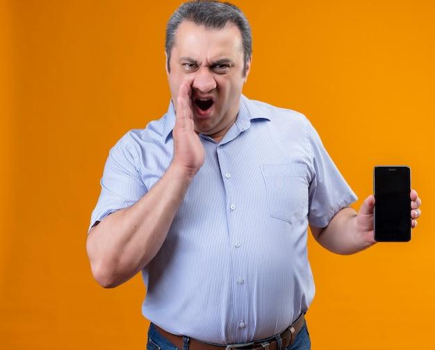 Homem de meia-idade zangado e descontente com uma camisa listrada azul gritando e mostrando o celular
