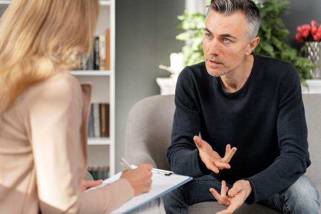 Homem de meio tiro falando com terapeuta