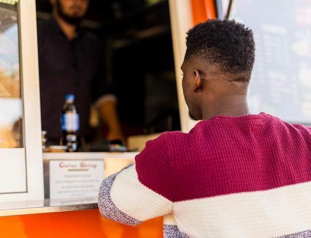 Homem de meio tiro fazendo pedido no food truck
