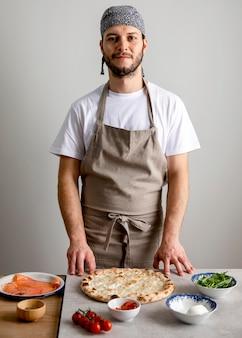 Homem de meio tiro parado perto da massa de pizza assada com ingredientes