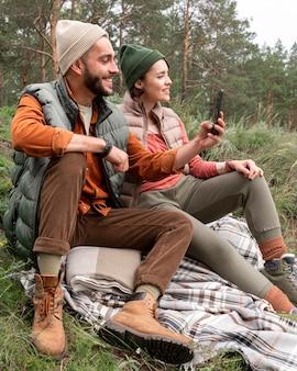 Homem de meio tiro sentado na grama tirando fotos com o telefone perto da namorada