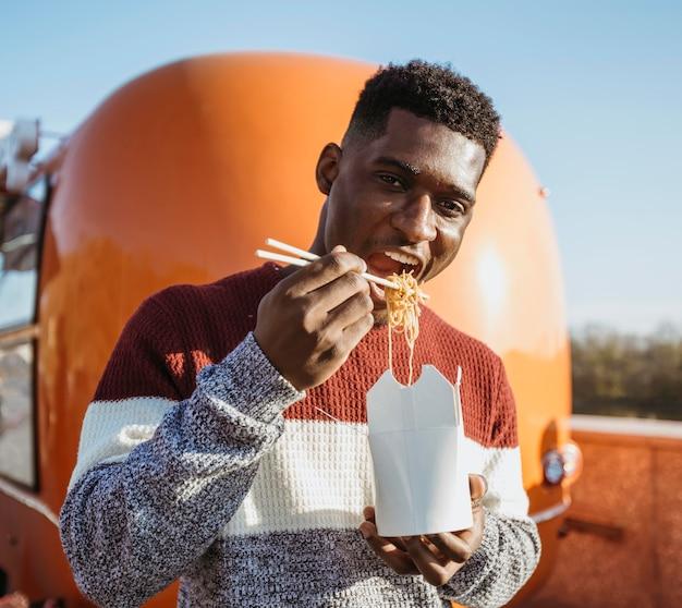 Homem de meio tiro sorrindo comendo comida chinesa perto de um caminhão de comida