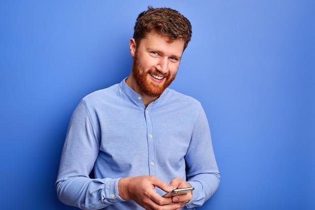 Homem de mente aberta está conversando com um amigo no smartphone, digitando mensagem, vestindo camisa formal azul, sorrindo