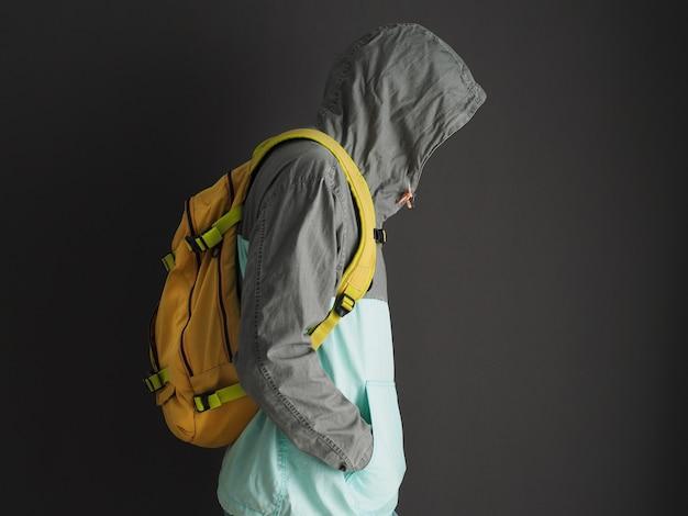 Homem de moletom cinza com capuz e mochila amarela. vista de perfil.