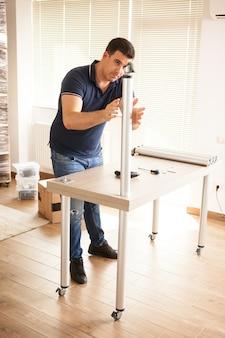 Homem de montagem de móveis para uma nova casa que eles compraram