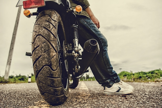 Homem de motociclista com sua moto (moto) na rua e bonito.