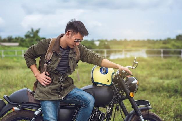 Homem de motociclista e moto com fundo do rio.
