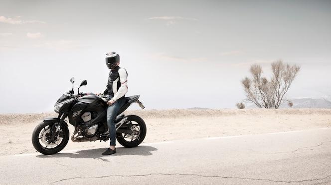 Homem de motociclista tiro no escuro, sentado na moto