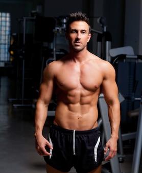 Homem de músculo em forma de fitness posando no ginásio