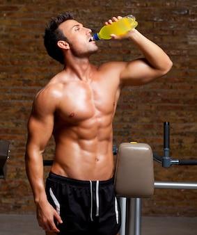 Homem de músculo no ginásio relaxado com bebida energética
