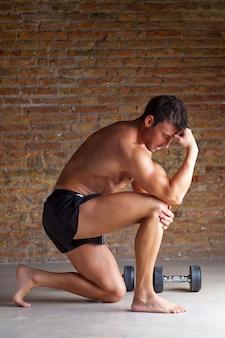 Homem de músculo pensando com postura de pensador