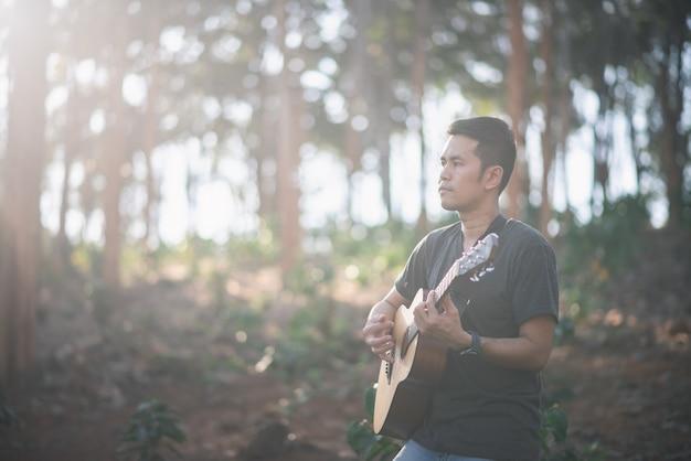 Homem de músico retrato com guitarra no forrest