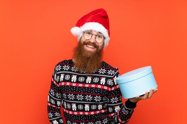 Homem de natal com barba longa, segurando um presente isolado parede vermelha