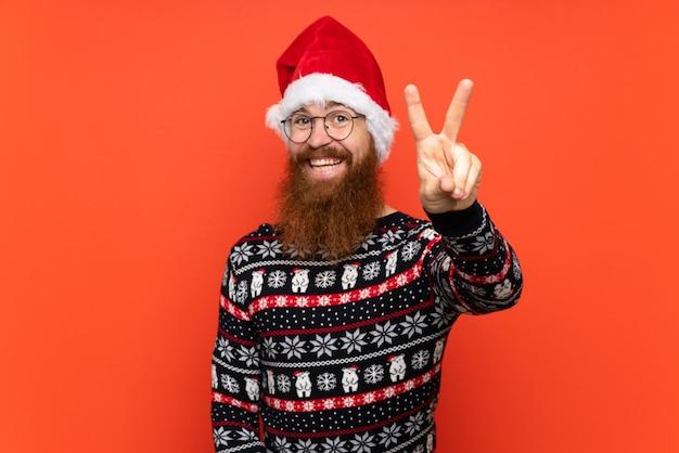 Homem de natal com barba longa, sobre fundo vermelho isolado, sorrindo e mostrando sinal de vitória