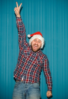 Homem de natal sorridente com chapéu de papai noel no estúdio azul