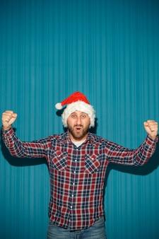 Homem de natal sorridente com chapéu de papai noel no fundo azul do estúdio
