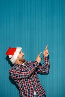 Homem de natal surpreso com chapéu de papai noel mostrando qualquer coisa no fundo azul do estúdio