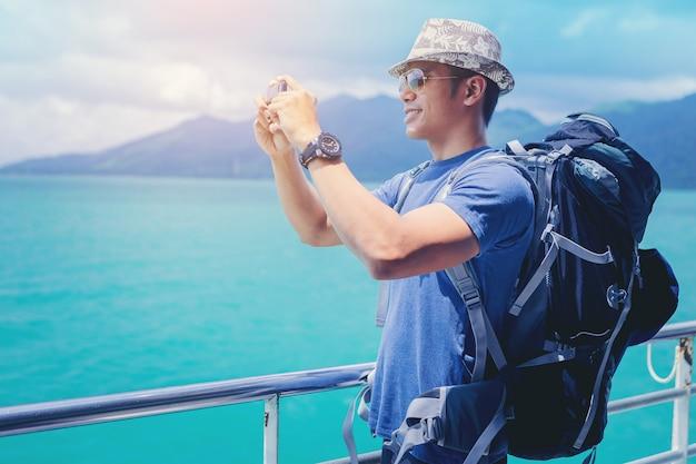Homem de navio de cruzeiro com mochila, usando telefone celular em viagens de férias no oceano.