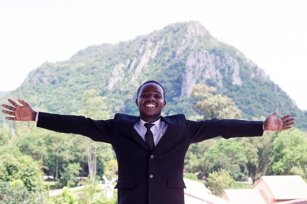 Homem de negócio africano bem sucedido com a montanha grande no fundo.