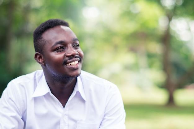 Homem de negócio africano na camisa branca que sorri e que senta-se fora com árvores verdes.