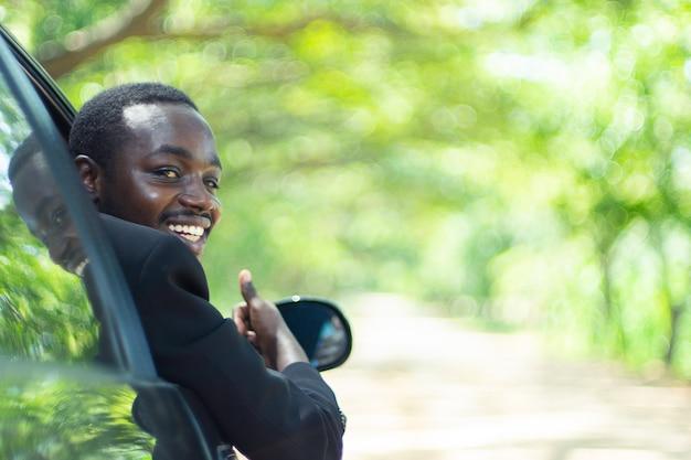 Homem de negócio africano que conduz e que sorri ao sentar-se em um carro com a janela dianteira aberta.