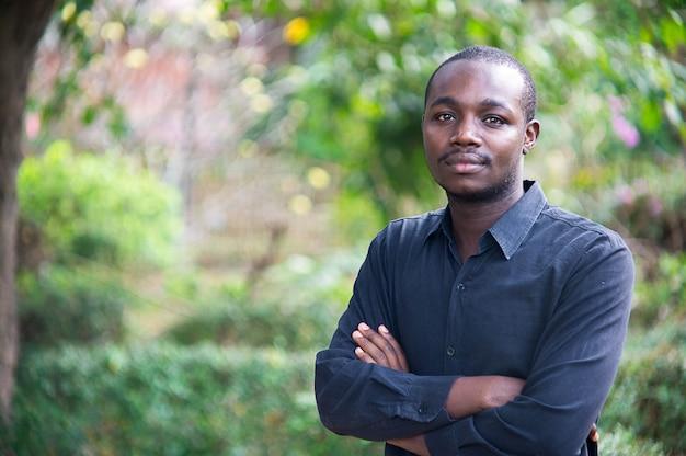 Homem de negócio africano que olha e que pensa na natureza verde.