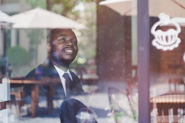 Homem de negócio africano que pensa e que olha no café.