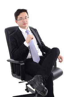 Homem de negócio asiático assentado na cadeira, isolado no fundo branco.