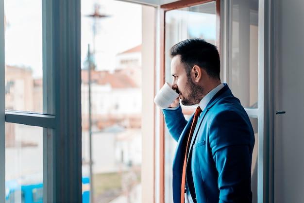 Homem de negócio bem sucedido que olha a cidade através da janela aberta ao beber de um copo.