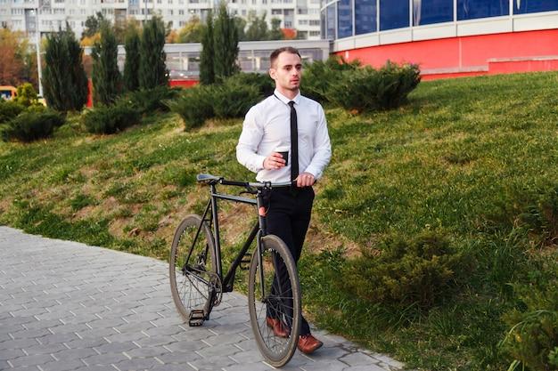 Homem de negócio com bicicleta que bebe o café do copo afastado.