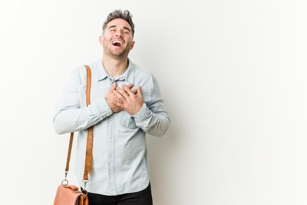 Homem de negócio considerável novo que ri mantendo as mãos no coração, conceito da felicidade.