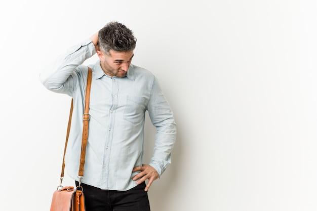 Homem de negócio considerável novo que toca atrás da cabeça, pensando e fazendo uma escolha.