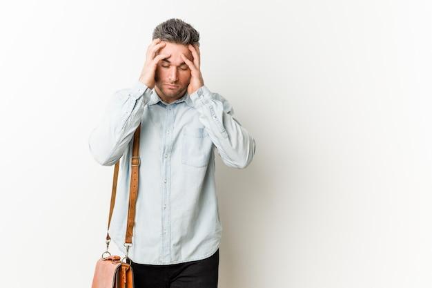 Homem de negócio considerável novo que toca em templos e que tem a dor de cabeça.